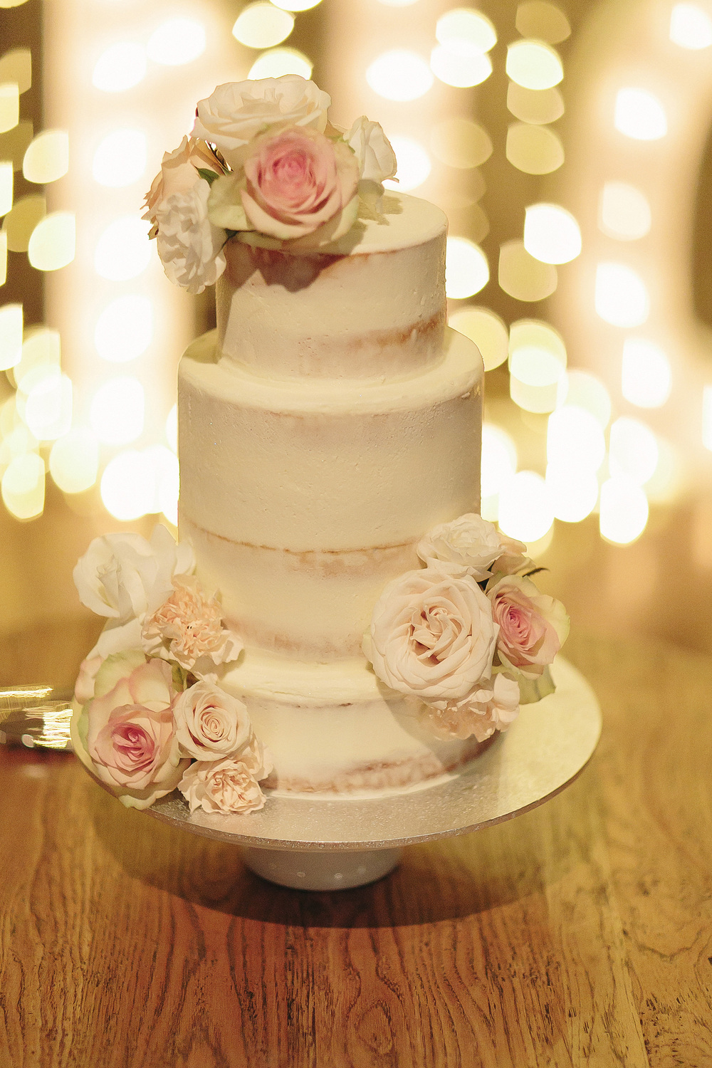 Three barely frosted tiers, and finished with fresh blooms - simply stunning!  Photo:  Juddrick Photography