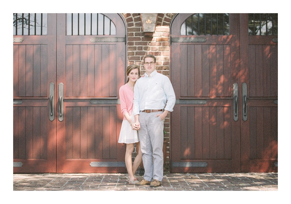 Charleston engagement photographer captures couple posing in front of carraige doors in downtown Historic Charleston
