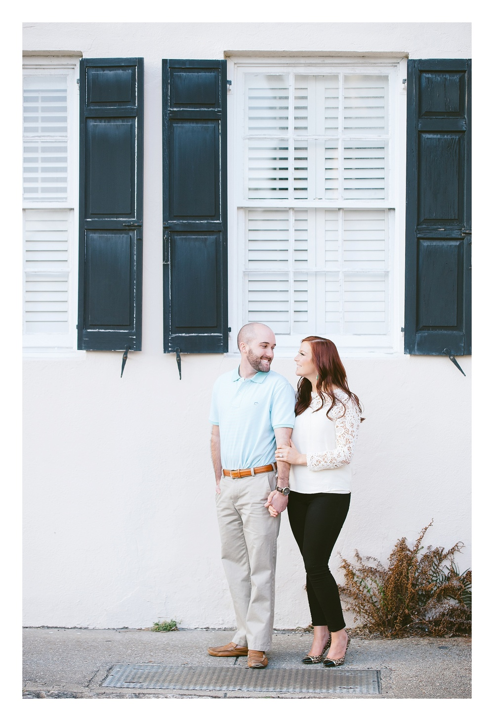 Charleston engagement photographer captures couple downtown Historic Charleston posing in front of a pink house