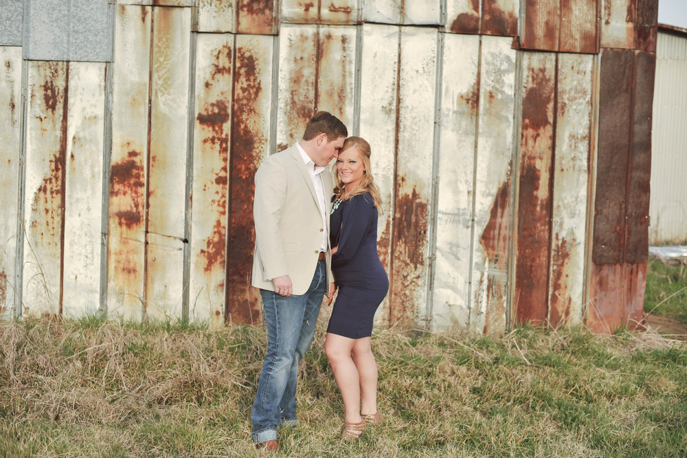 Charlotte engagement photographer captures couple hugging in a cotton field in Charlotte, NC during their engagement session
