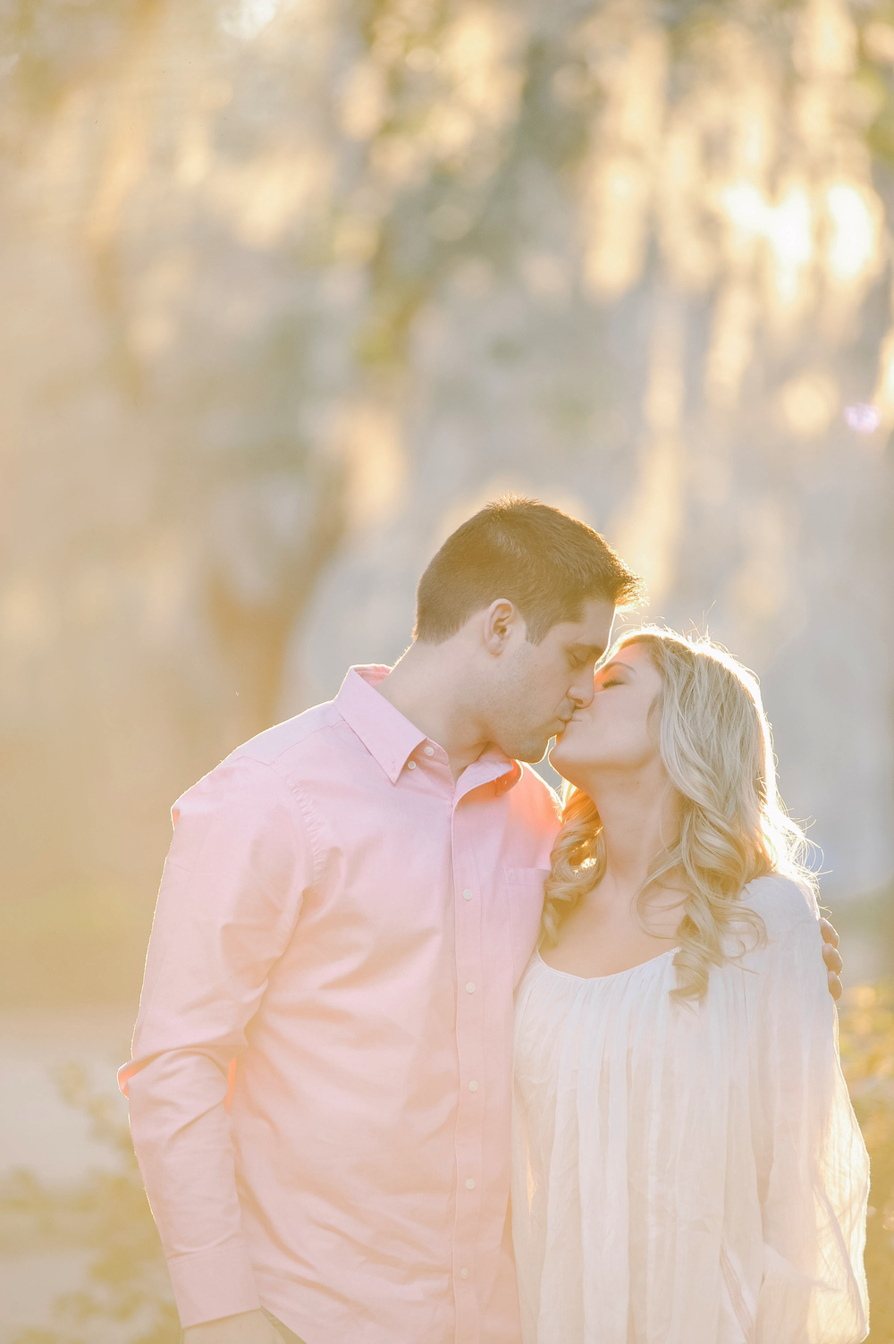 Charleston engagement photographer captures couple under Spanish moss in Charleston, SC at sunset.