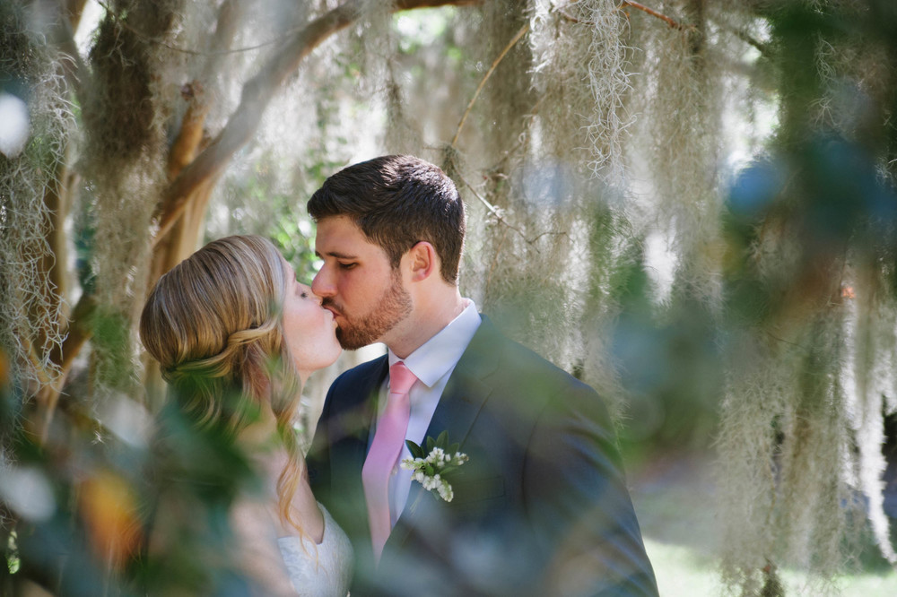couple kiss under spanish moss at Legare Waring House wedding designed by OOH! Events