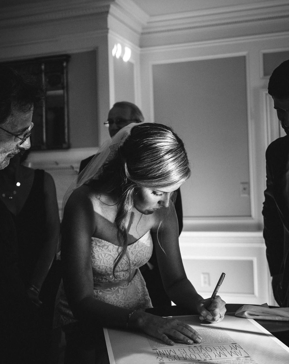bride signs ketubah at Legare Warring House wedding venue