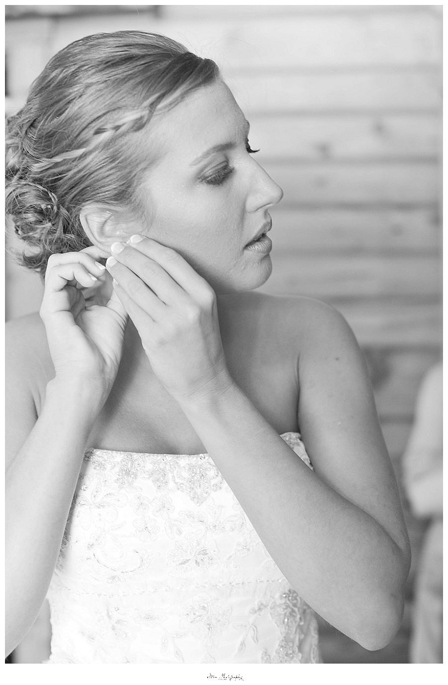 charleston wedding photo of bride putting in earrings