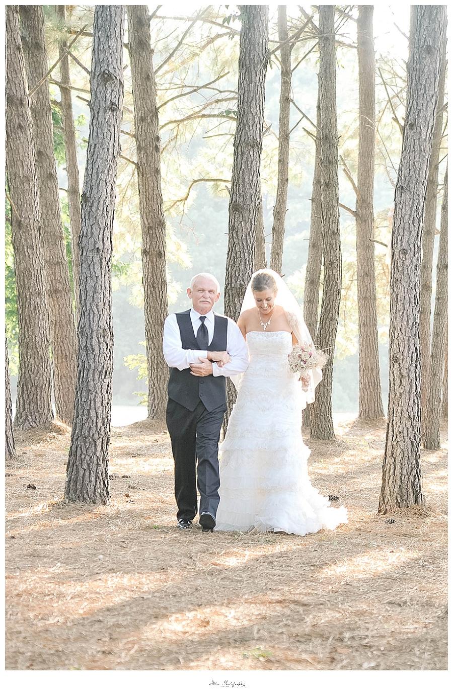 photo of grandfather walking bride down pine tree aisle at Charleston wedding