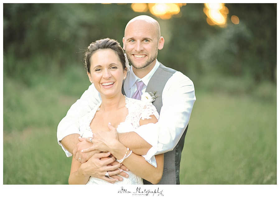 groom wraps arms around bride during portraits at brakefield wedding