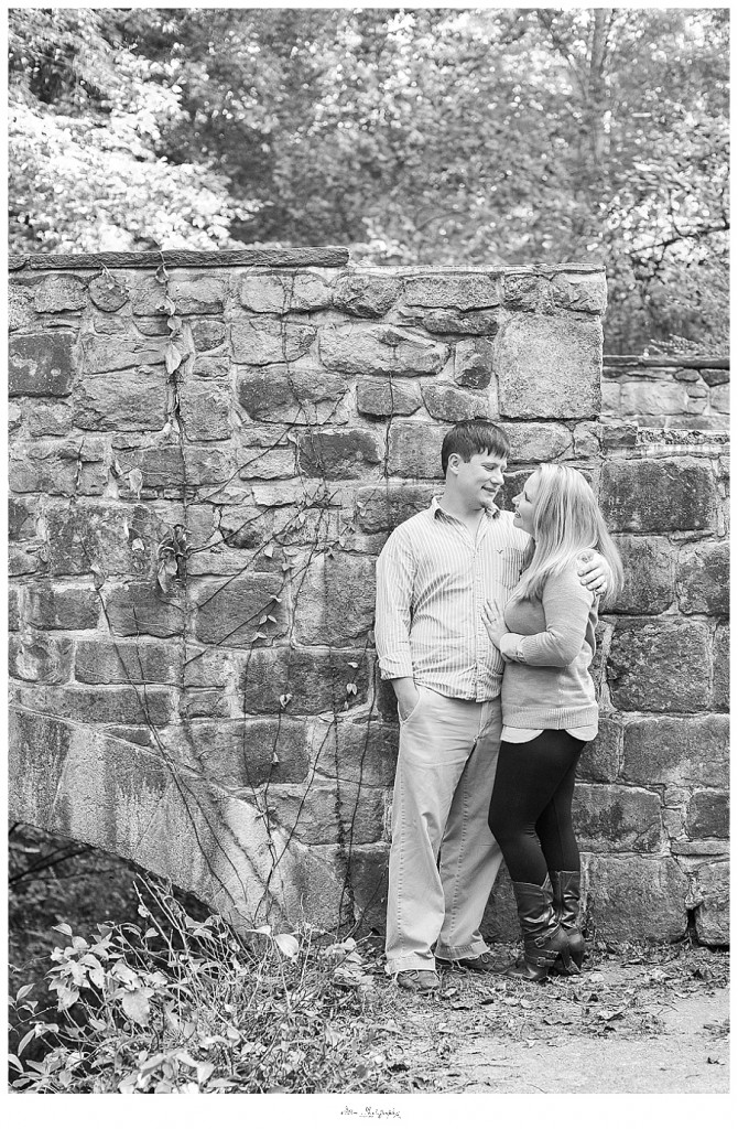 black and white engagement picture, couple stands against stone wall