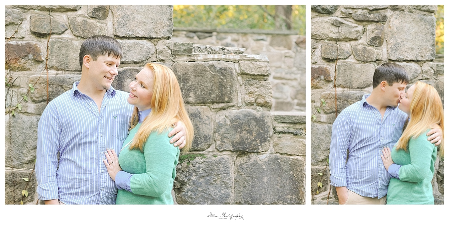 couple poses for engagement picture against stone bridge at lansford canal
