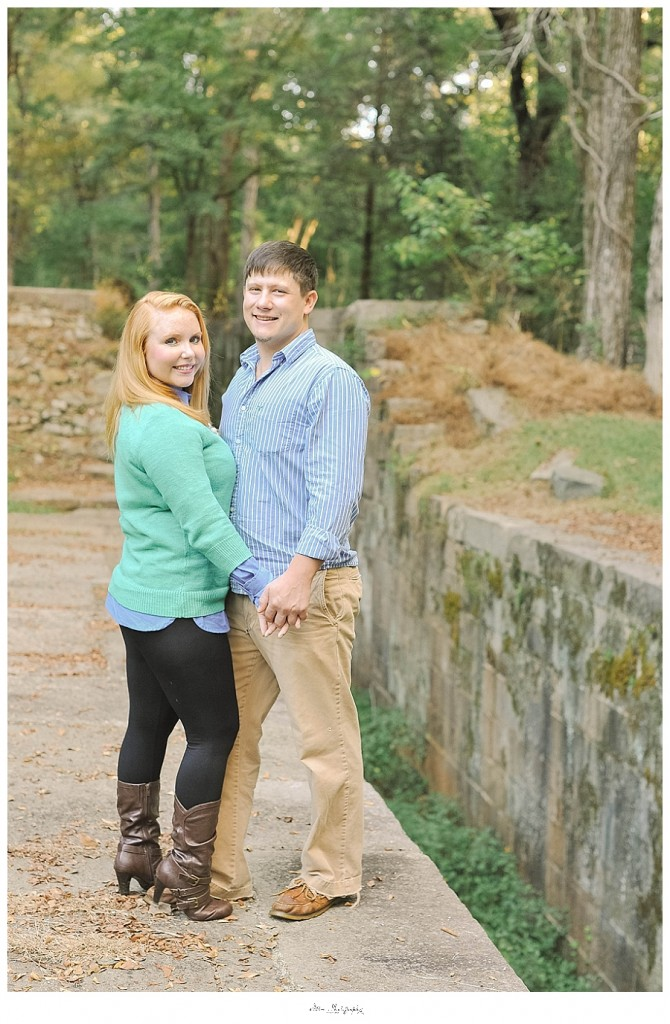 couple poses for engagement picture against stone bridge at lansford canal outside of charlotte nc