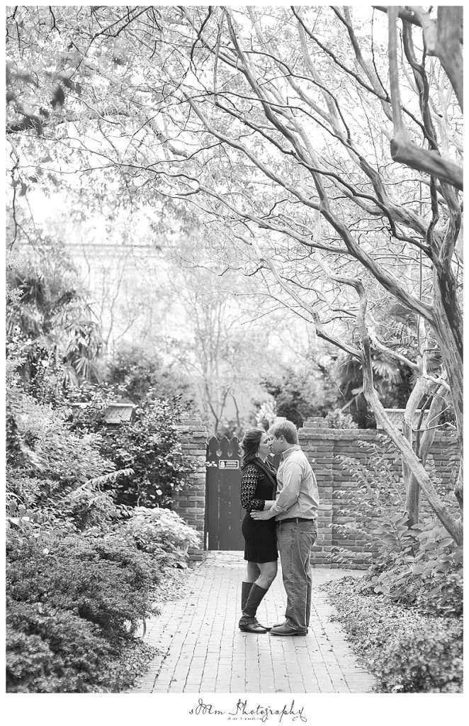 black and white photo of couple kissing on path at USC in Columbia, SC