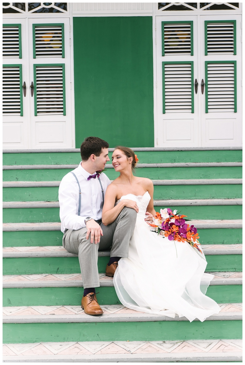 bride and groom sit on steps of Aruba courthouse