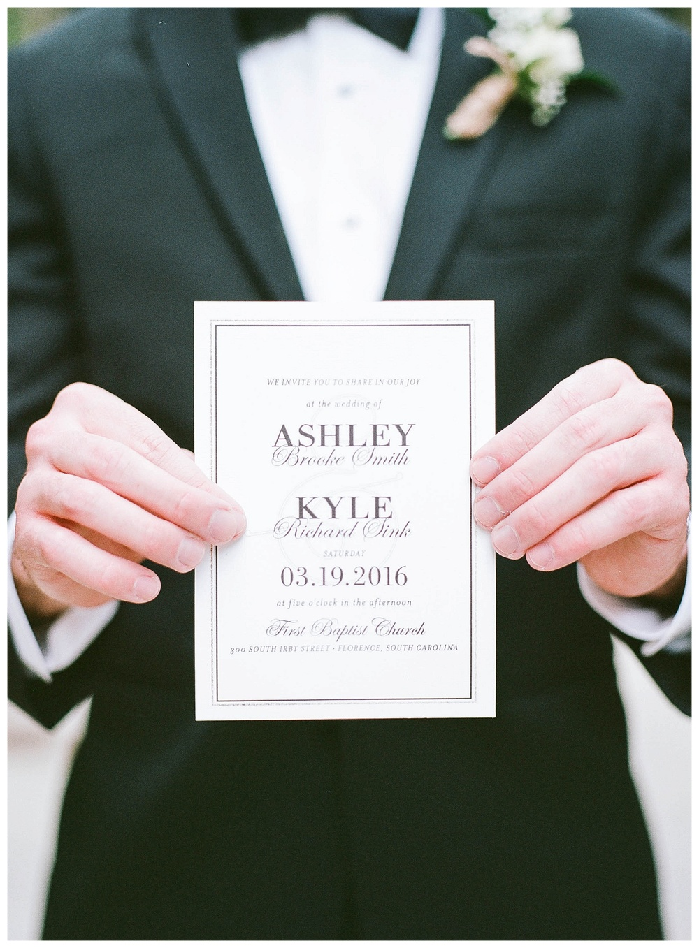groom holds invitation for wedding at Hotel Florence, SC