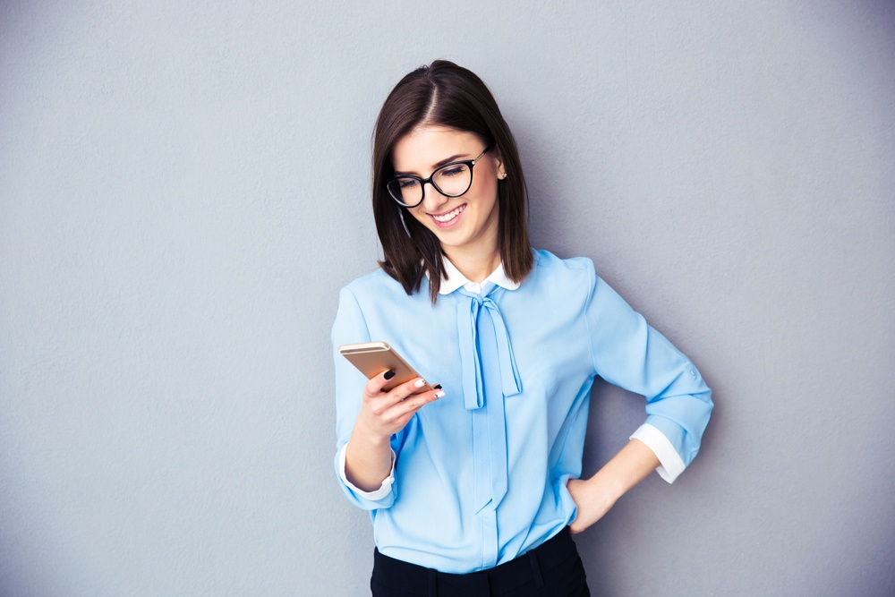 Smiling businesswoman using smartphone over gray background. Wearing in blue shirt and glasses..jpeg