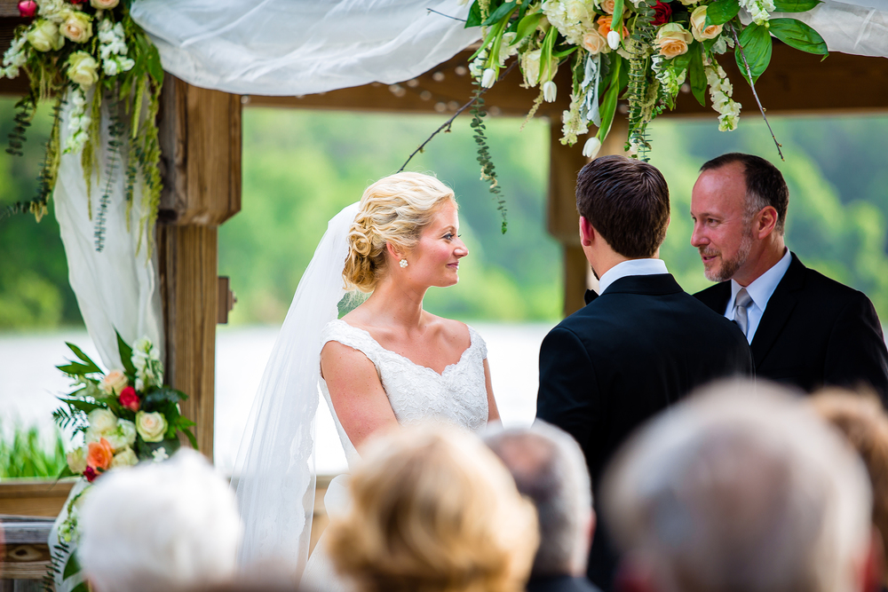 Wedding ceremony bride and groom lakeside greenery flowers