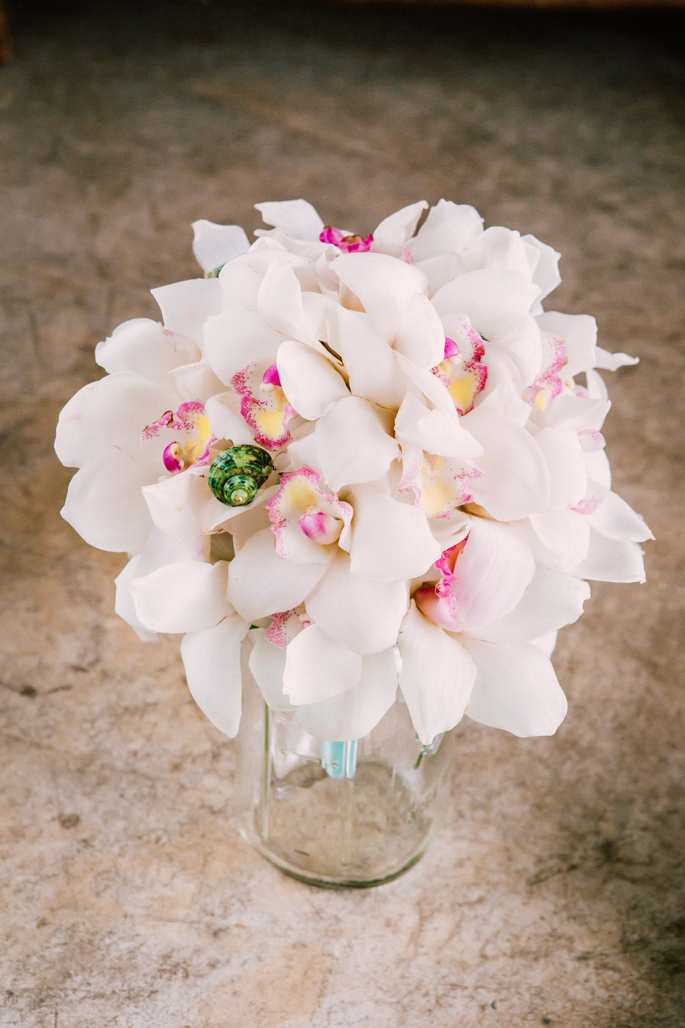 Mermaid bride bouquet, made with white and pink dendrobium orchids, green seashells, and tied in blue satin, made by Simple Roses of Daytona Beach.