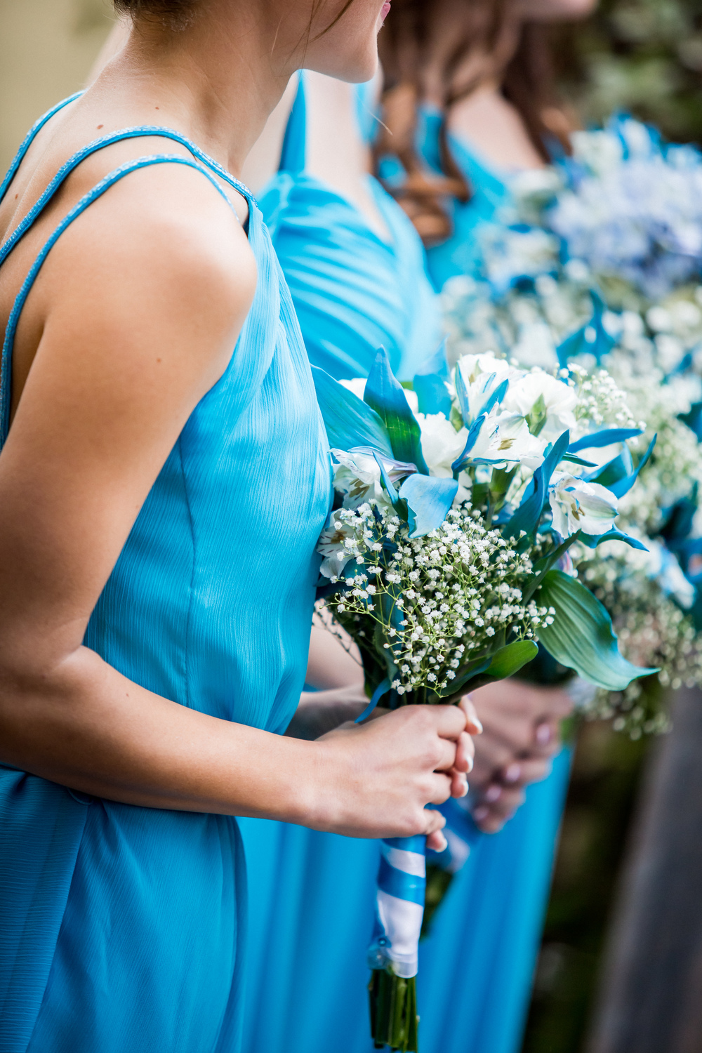 Sky blue wedding bouquet, with white alstromerias, baby's breath, and blue flower petals.