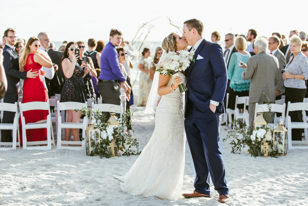 Longboat Key Club wedding ceremony kiss, florals by Victoria Blooms