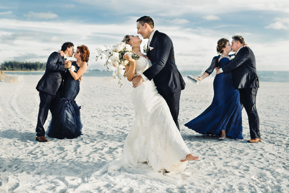 Bride and groom kissing with parents creative family wedding photos Longboat Key club beach wedding