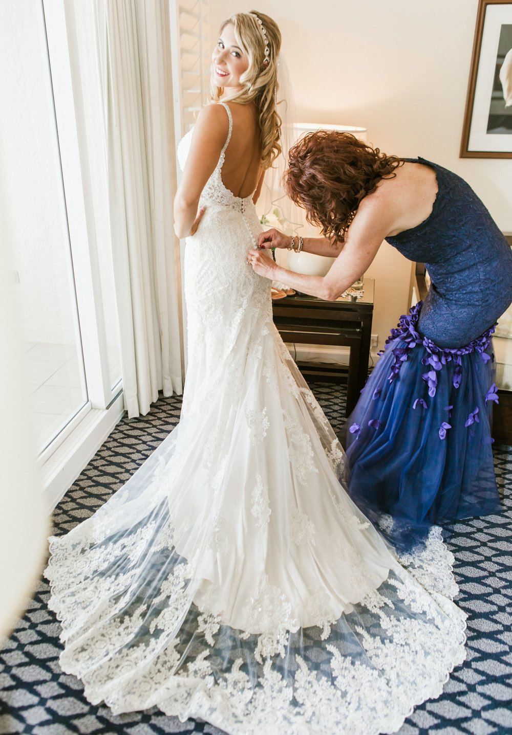 Longboat Key Club Beach Wedding - Mother helping bride into lace gown