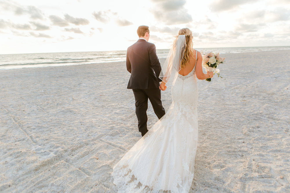 Sarasota beach wedding bride + groom walking into the sunset