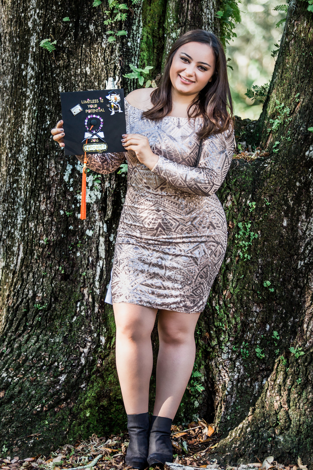 Harry Potter style fun UCF grad photos with golden glitter and a book in Langford Park, downtown Orlando, Florida