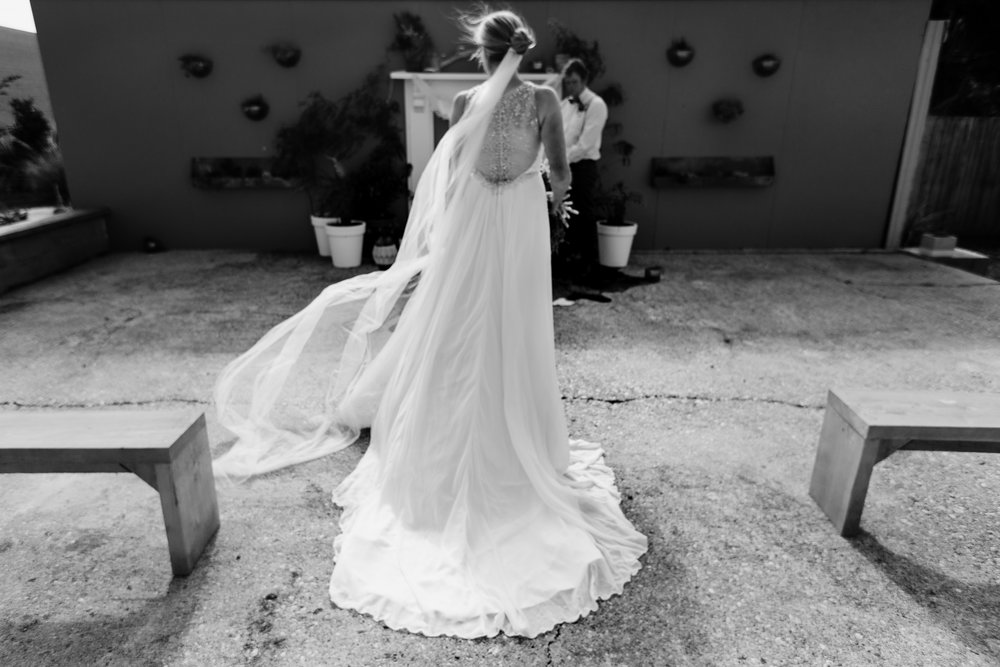 Silver beaded back detail wedding gown with chiffon skirt and full length veil at a destination wedding at the Port Molyneux School