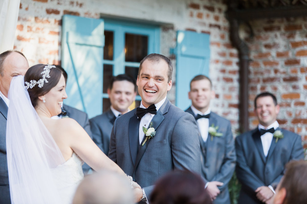 Bride & Groom laughing at their Casa Feliz Winter Park Wedding during the ceremony, coordinated by Adore Amor Wedding Planning