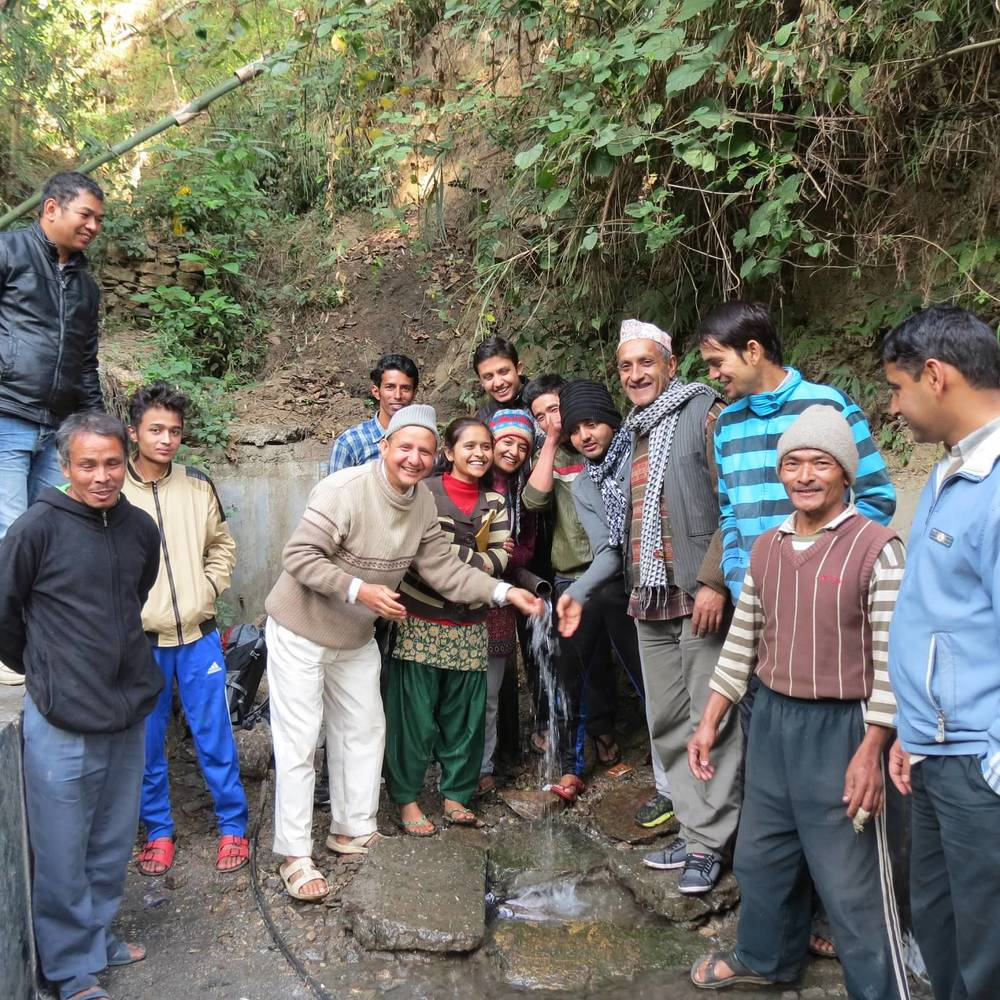 Khosli Dhara User's Committee at the spring source site before the implementation of the new system. The existing structure had fallen into disrepair, and was not capturing all of the spring's flow or adequately protecting the water from surface contamination sources.
