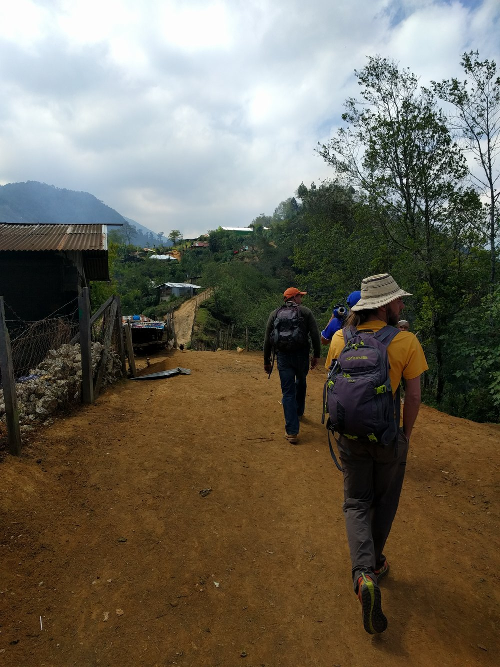 RMP member Dave Caley, Diego, and mason Christobal walking through Sumal Grande to see the progress of the construction.