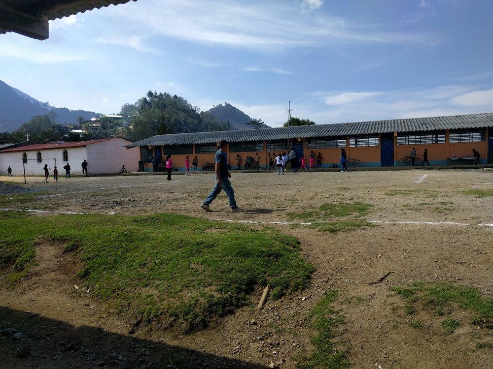 A girls futbol match in the school yard.
