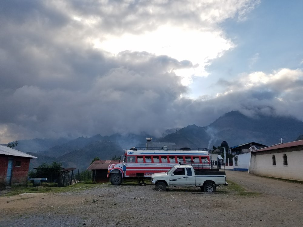 The mountains near Sumal Grande on a cloudy morning, featuring one of the chicken buses that regularly serves the community.