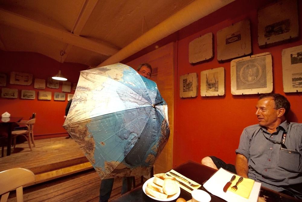 Misha mostra seu guarda-chuva com o pólo norte, por onde costuma realizar expedições com seu helicóptero.