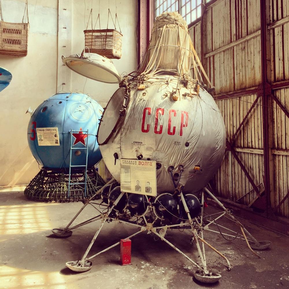 Cápsula espacial meio que jogada num canto de um grande galpão.