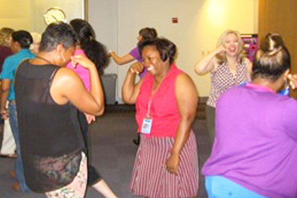 corporate group engaged in laughing yoga team building event