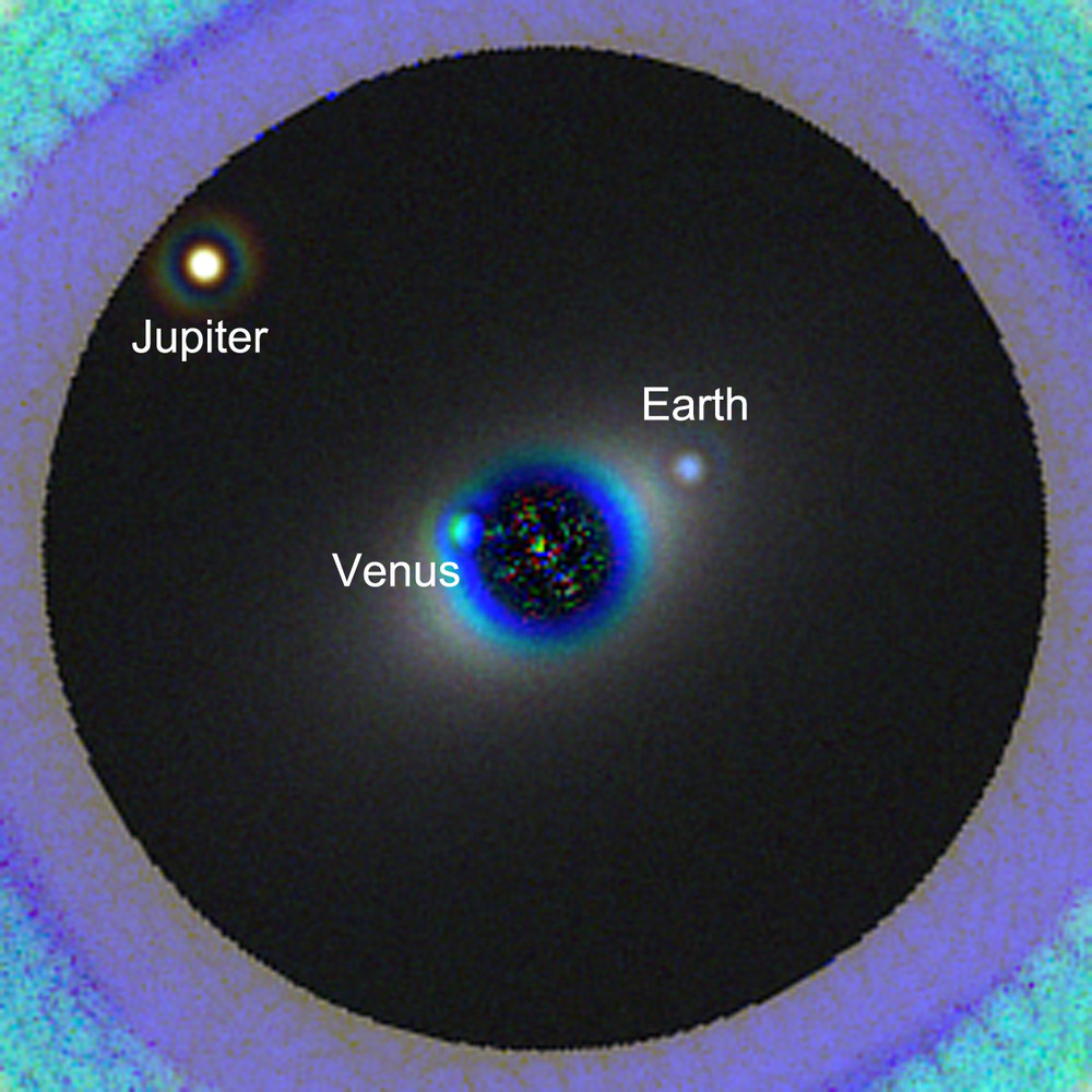 A simulated image of a solar system twin as seen with the proposed  High Definition Space Telescope (HDST) . The star and its planetary system are shown as they would be seen from a distance of 45 light years. The image here shows the expected data that HDST would produce in a 40-hour exposure in three filters (blue, green, and red). Three planets in this simulated twin solar system - Venus, Earth, and Jupiter - are readily detected. The Earth's blue color is clearly detected. The color of Venus is distorted slightly becuase the planet is not seen in the reddest image.  The image is based on a state-of-the-art design for a high-performance coronagraph (that blocks out starlight) that is compatible for use with a segmented aperture space telescope.   Image credit: L. Pueyo, M. N'Diaye (STScI)