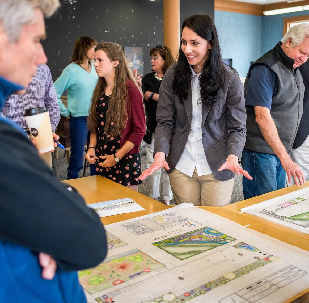 Stephanie Maliki '18 (right) and Acadia LeBlanc '18 (left) explain and present their permaculture designs for the town to the Franklin Falls community.  Photo by Michael Seamans