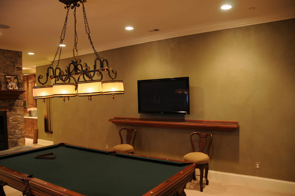 """The billiard room is a prime entertainment area with a wall mounted TV, ultra high-performance in-ceiling speakers, and a 24"""" in-wall touch screen on the opposite wall"""