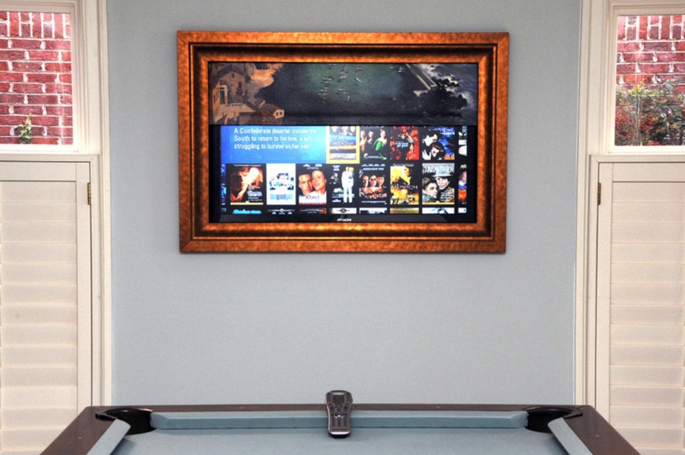 With a push of a button, the artwork is lifted, revealing the television when entertaining guests