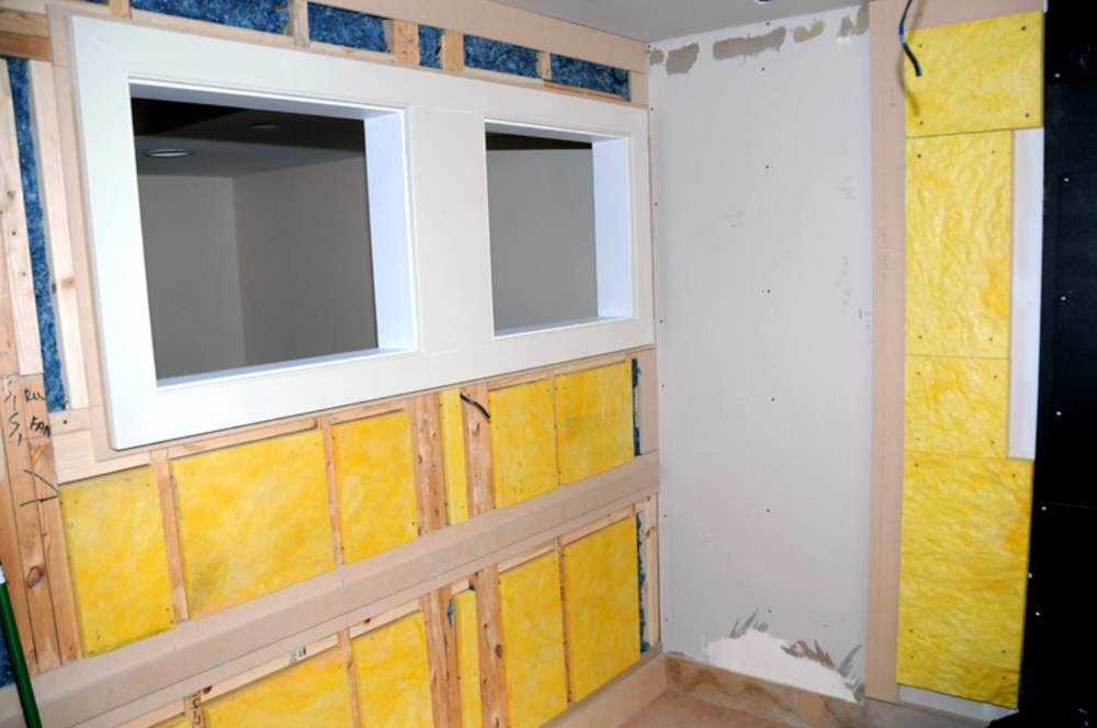 Acoustic insulation was placed inside the wall cavity between framing members to yield as much finished floor space as possible
