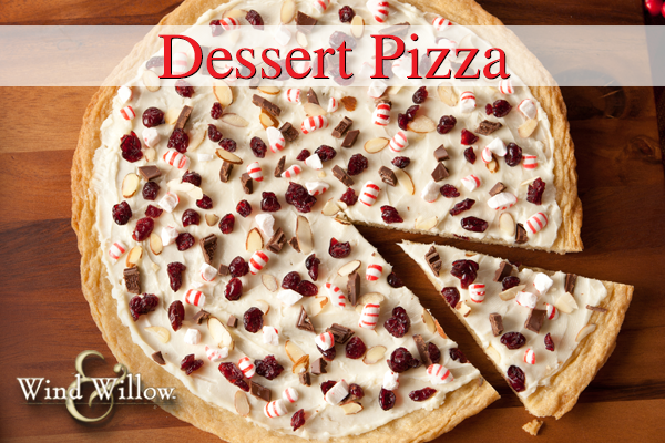 "DESSERT PIZZA Wind & Willow Chocolate Chip Cheeseball & Dessert Mix 8 oz cream cheese 4 Tbs butter 1 package refrigerated cookie dough  Heat oven to 350°F. Press dough evenly in bottom of a greased 12"" round pan to form crust. Bake 16 to 20 minutes or until golden brown. Set aside and let cool. Meanwhile combine Cheeseball Mix with cream cheese and butter until smooth. Spread mixture on crust and sprinkle with Topping packet. Top with nuts, seeds and candies! Refrigerate until ready to serve!    We topped this Holiday Dessert Pizza with cranberries, chocolate, and crushed peppermints."