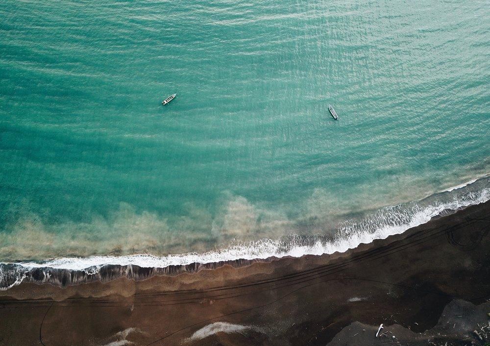 the black sand beaches in front of Sansara Resort await....