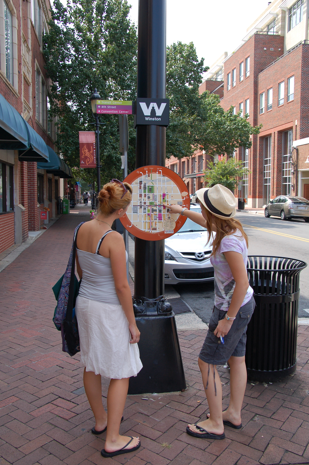 Passers-by checking out personal map station in Winston-Salem.