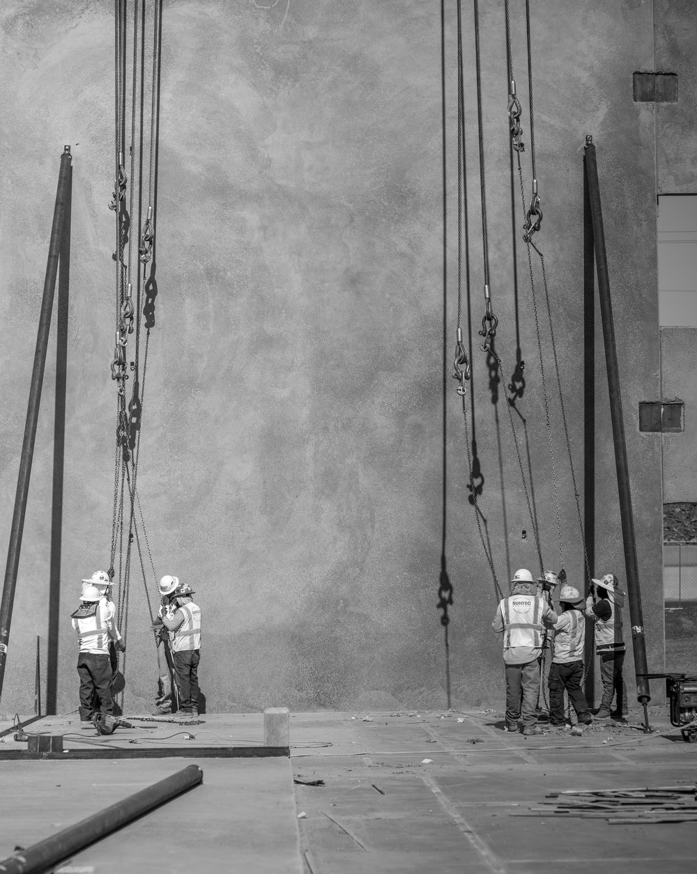 CLICK TO VIEW GALLERY     Workers re-setting chains suspended from crane above