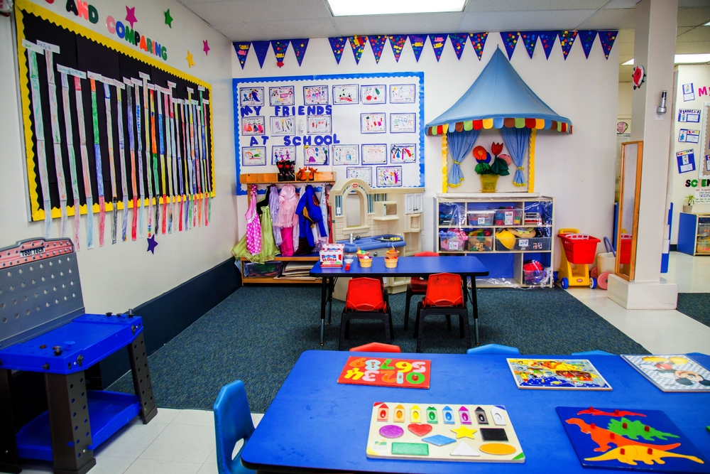 The play house area of the Daisy Room, which is open every morning with a different choice of dramatic play. Tables are set with puzzles, manipulatives, or fine motor activities.