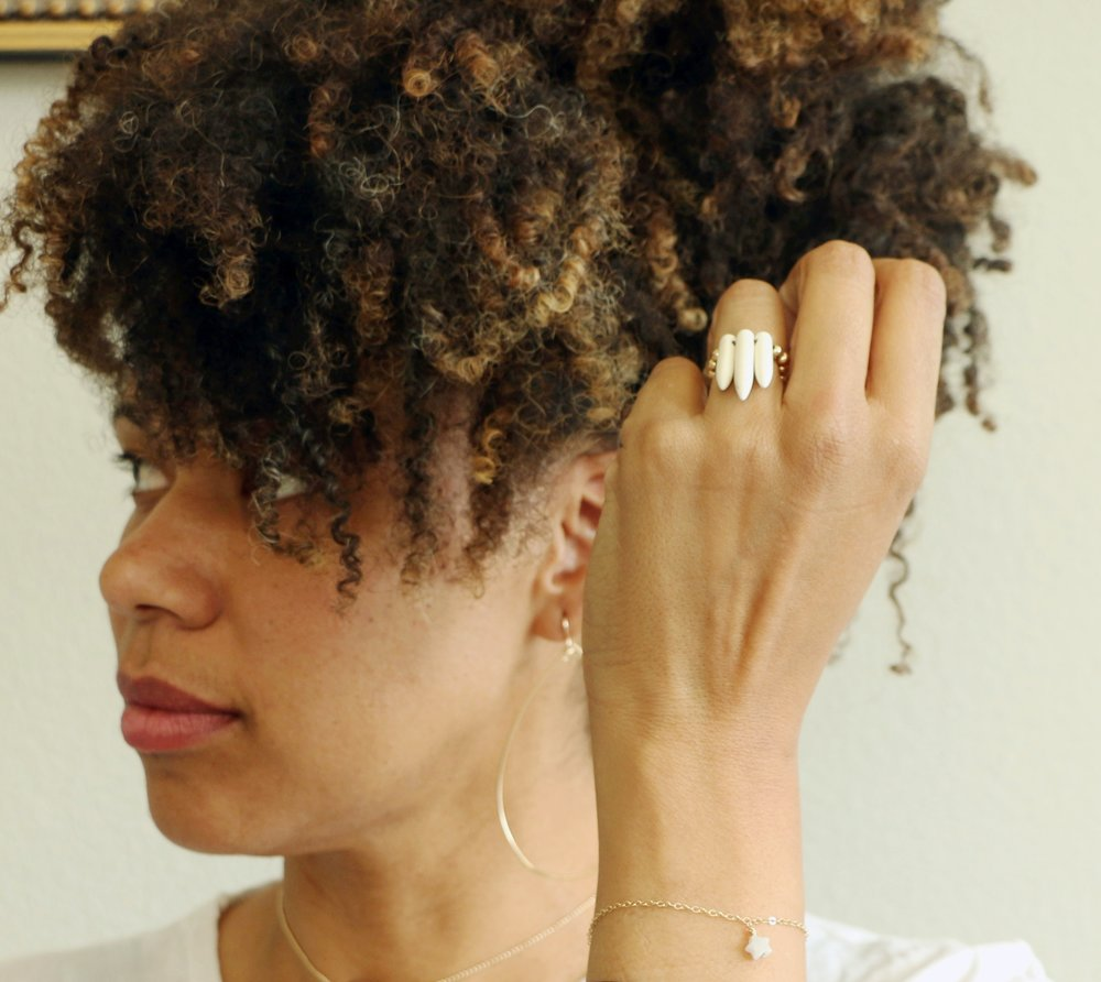 aleia wears our morning doves ring, candy bracelet with mother of pearl star and large freeform teardrop earrings.