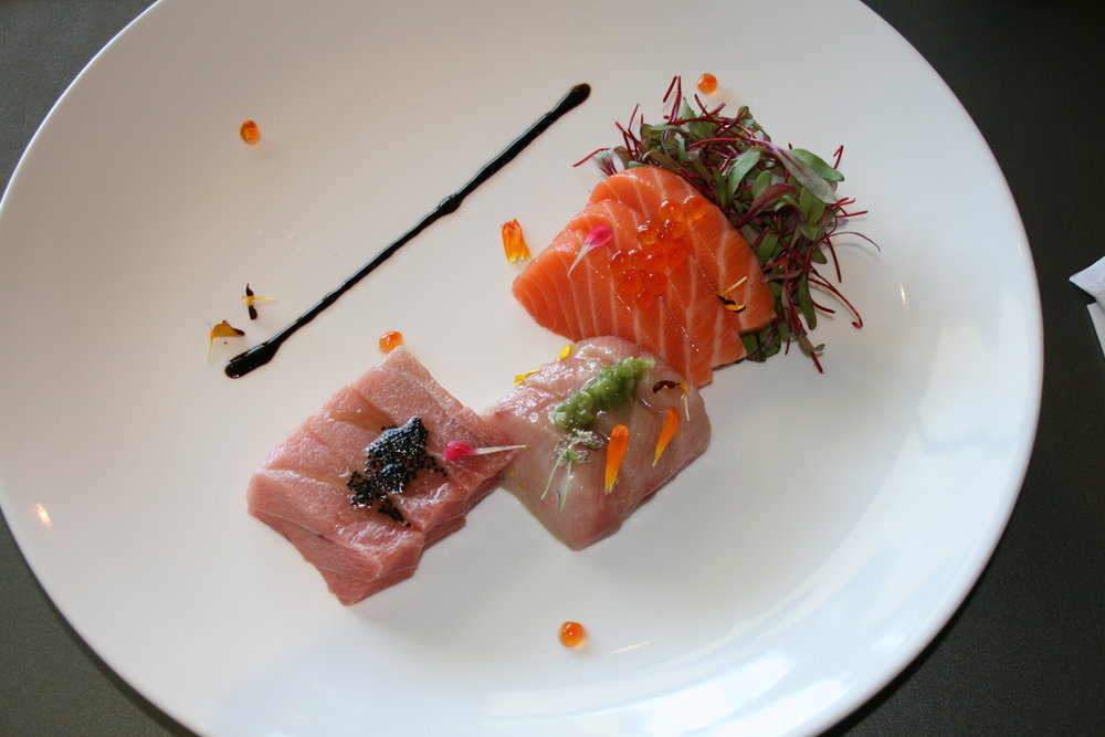 SAMPLE THE SEA  The Arigato sashimi sampler is laden with thick slices of the freshest bluefin tuna, yellowtail, and salmon; topped with salty masago; and accompanied by tender microgreens and a drizzle of balsamic reduction.
