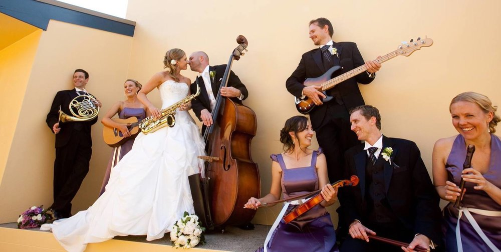 You might have noticed that the bass player in this picture is Foxey, our bass player. This is not him moving in on a bride at a wedding, this is a photo from his own wedding. We promise.