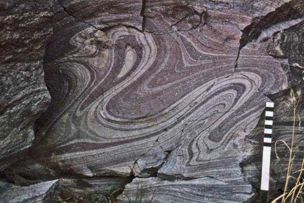 "Inclined post-depositional flow folds superimposed upon a syn-depositional sheath fold (the ""purple wet pull-over"")"