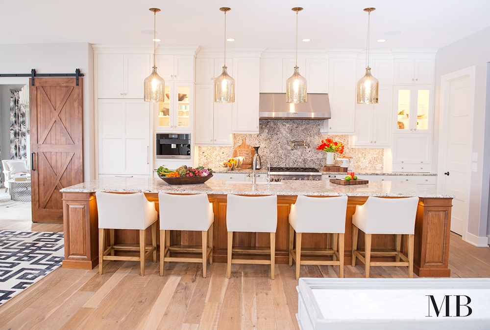 Warmth, style and functionality were top on the list for this kitchen. Integrated appliances keep the design cohesive and the symmetry of the cabinetry keep it feeling orderly. Beautiful finishes give this space a transitional aesthetic.