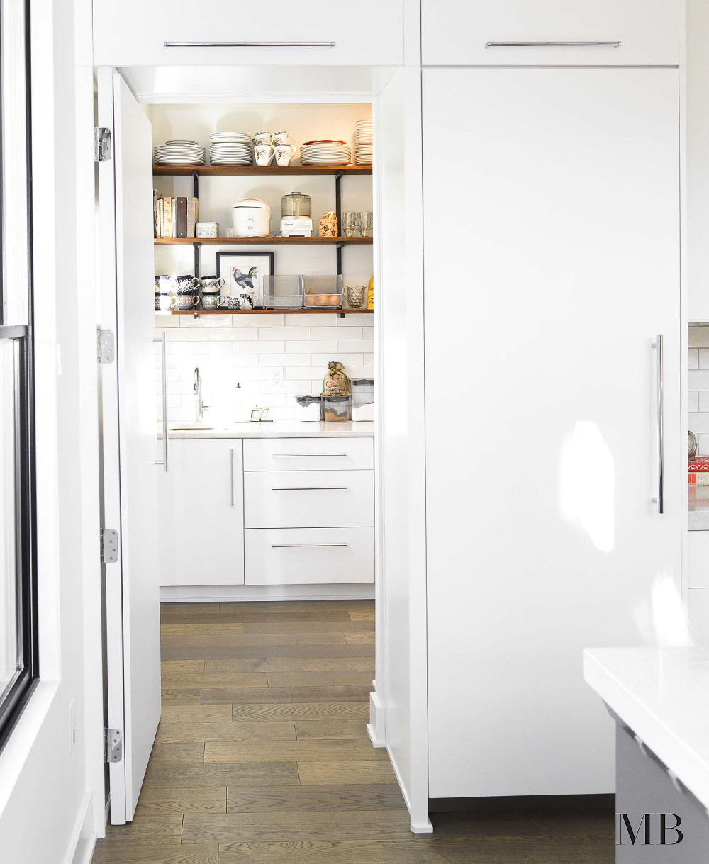 This sleek and modern kitchen remains as functional as a more traditional space by this walk-in hidden pantry. While the main space stays minimal and clear of too many objects, the pantry is full of useful kitchen objects at an arms length. This home was designed with a modern farmhouse style and we kept that going with subway tile and wooden shelves.